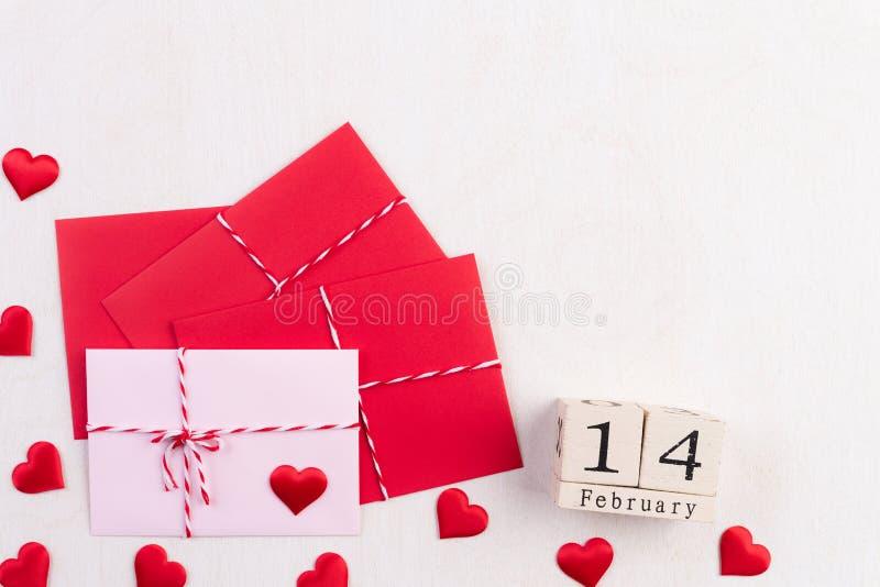 Valentinsgrußtag und Liebeskonzept Rote Herzen und rote rosa Buchstabeabdeckung und 14. Februar-Text auf Holzklotz auf weißem höl lizenzfreies stockfoto