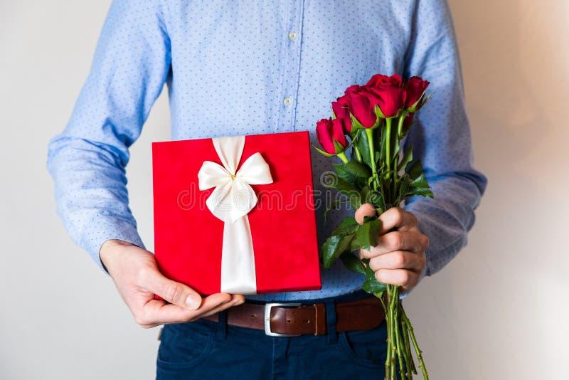 Valentinsgrußtagesüberraschung, Liebe, gut aussehender Mann, der romantisches Geschenk und Blumenstrauß der roten Rosen hält lizenzfreie stockbilder