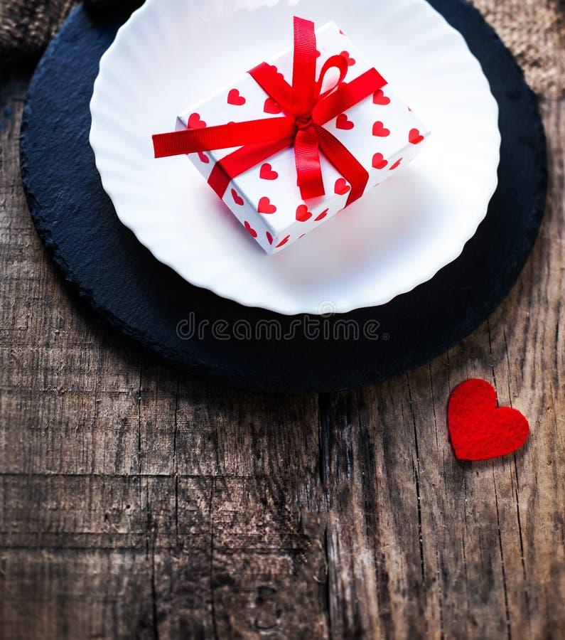 Valentinsgrußtagesgedeck mit weißer Platte, Gabel, Messer und r stockbilder