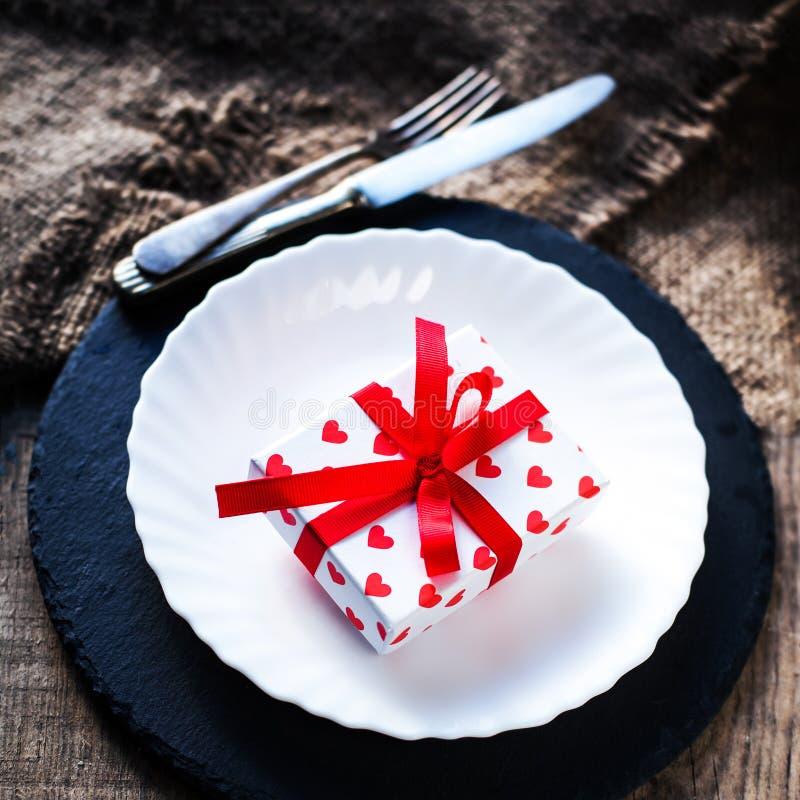 Valentinsgrußtagesgedeck mit weißer Platte, Gabel, Messer und r lizenzfreie stockfotos