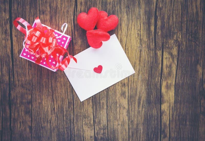 Valentinsgrußtagesgeschenkboxrosa auf hölzerner Umschlagliebespost Valentine Letter Card mit rotem Herz-Liebeskonzept stockfotos