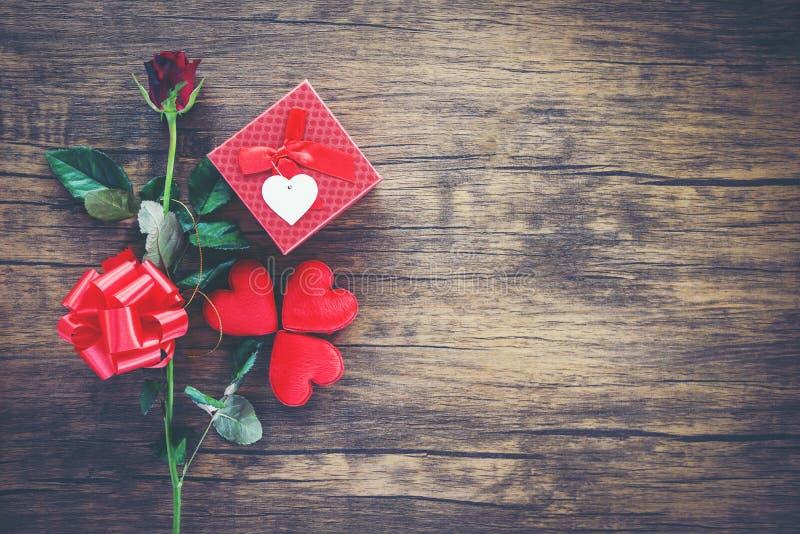 Valentinsgrußtagesgeschenkboxrot auf hölzernem rotem Herz-Valentinsgrußtagesrotem rosafarbenem Blumen- und -Präsentkartonbandboge stockbilder