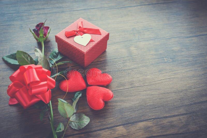 Valentinsgrußtagesgeschenkboxrot auf hölzernem rotem Herz-Valentinsgrußtagesrotem rosafarbenem Blumen- und -Präsentkartonbandboge lizenzfreie stockfotografie