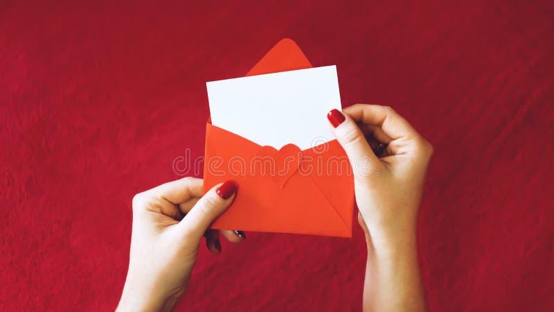 Valentinsgrußtagesgrußkarte, Modell mit Kopienraum leere weiße Karte und roter Umschlag auf rotem Hintergrund lizenzfreies stockfoto