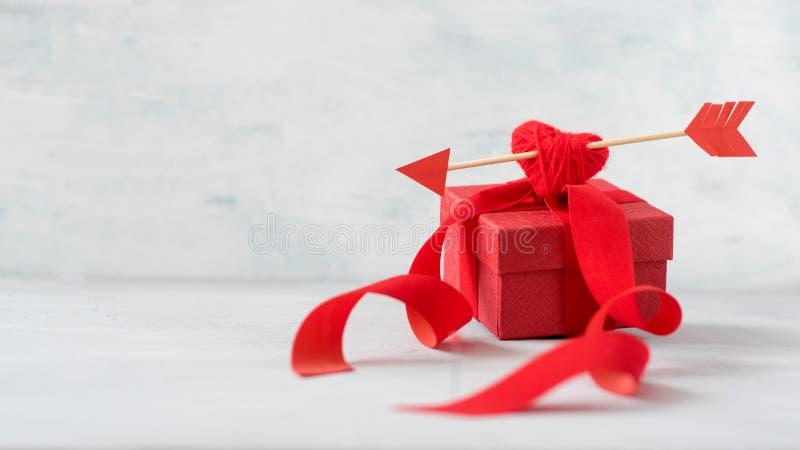 Valentinsgrußtagesgrußkarte, Modell mit Kopienraum Rote Geschenkbox mit Fadenherzen, Cupid' s-Pfeil, Bänder auf Grau lizenzfreie stockfotografie