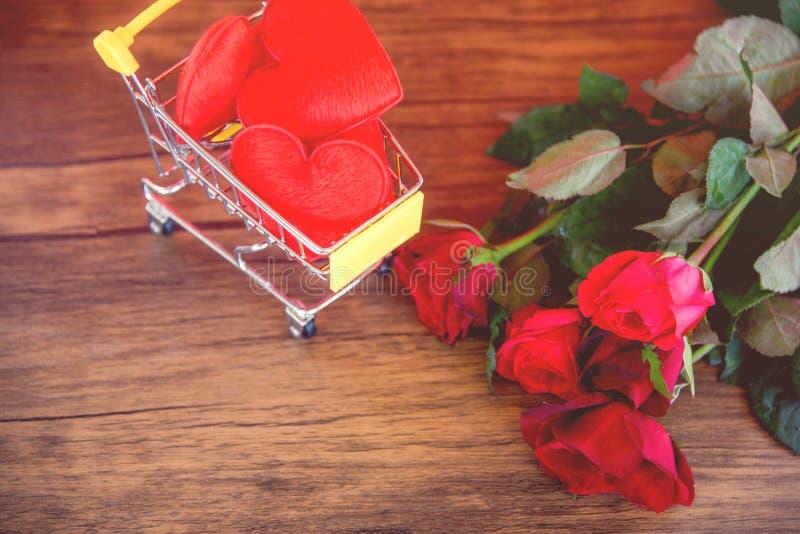 Valentinsgrußtageskaufendes rotes Herz am Einkaufswagenliebeskonzept Einkaufsfeiertag für Liebe Valentinsgrußtagesrote Rosen blüh stockbild