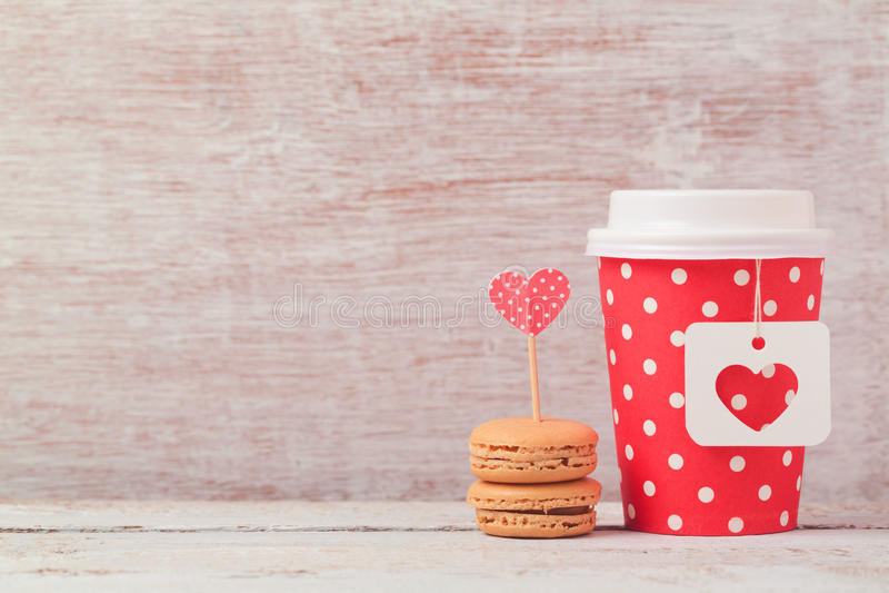 Valentinsgrußtageskonzept mit Papierkaffeetasse und macarons Romantische Kaffeestube stockfoto