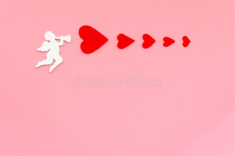 Valentinsgrußtageskonzept mit weißem Amorengelsschießen mit roten Herzen auf einem rosa Hintergrund Kopieren Sie Raum f?r Text lizenzfreie stockfotos