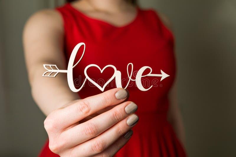 Valentinsgrußtagesliebeszeichen, Schönheit im roten Kleid, das in der Hand Liebesamorpfeil, Abschluss oben hält lizenzfreies stockfoto