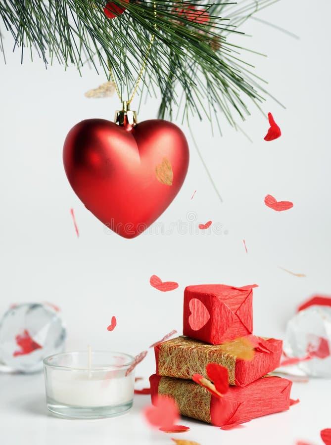Valentinsgrußtagesrot und Goldgeschenkbox unter Herzen formten Konfettis lizenzfreie stockfotografie