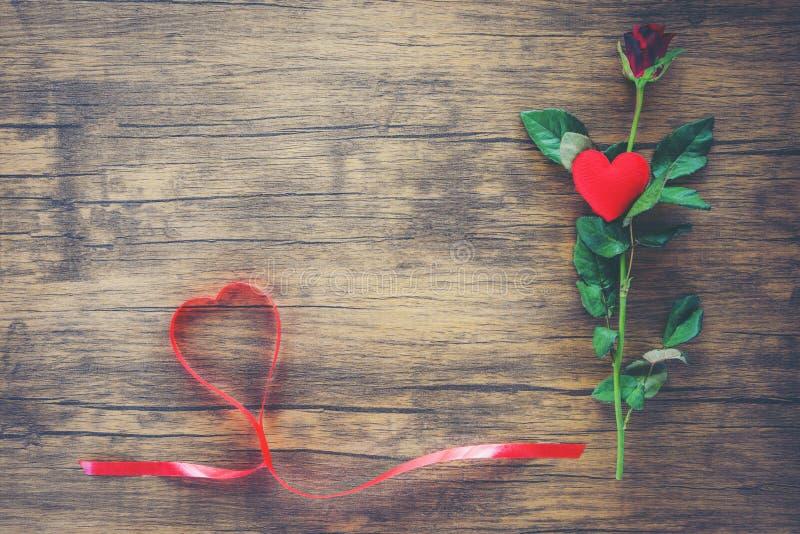Valentinsgrußtagesrote rosafarbene Blume auf hölzernem Hintergrund/rotem Herzen mit Rosen stockbilder