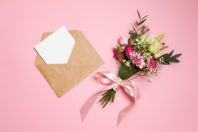 Valentinsgrußtageszusammensetzung: Blumenstrauß von Blumen, Kraftpapier-Umschlag mit Grußkartenlage am rosa Hintergrund Templa Ka stockbild