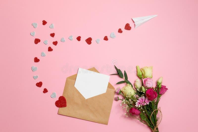 Valentinsgrußtageszusammensetzung: Blumenstrauß von Blumen mit Bandbogen, Kraftpapier-Umschlag mit leerer weißer Karte für Ihren  stockfotografie