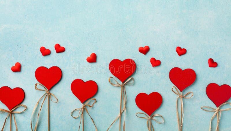 Valentinstag Grußkarte oder Banner Verschiedene rote Herzen auf blauem Hintergrund oben Flachlage lizenzfreie stockfotografie