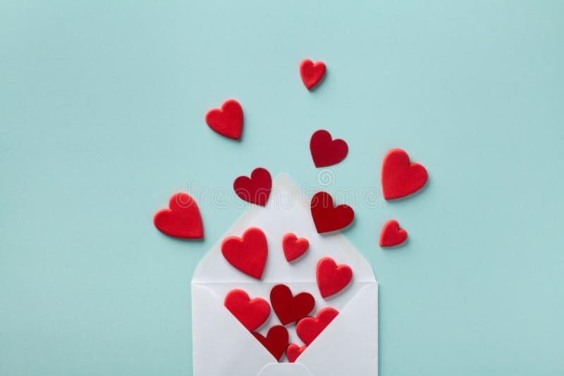 Valentinstag Grußkonzept Umschlag und rote Herzen auf blauem Hintergrund oben Flachlage stockbilder