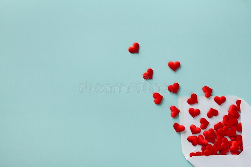 Valentinstag-Konzept Umschlag und rote Herzen auf blauem Hintergrund oben Flachlage lizenzfreie stockbilder