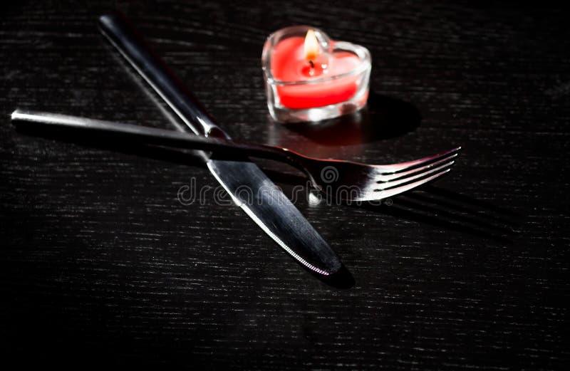 Valentinstaggedeck mit Messer, Gabel, rotes brennendes Herz formte Kerze lizenzfreies stockbild