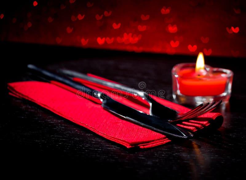 Valentinstaggedeck mit Messer, Gabel, rotes brennendes Herz formte Kerze lizenzfreie stockfotos