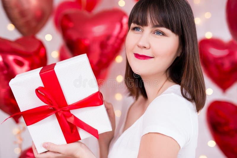 Valentinstagkonzept - Abschluss herauf Porträt der glücklichen träumenden Frau mit Geschenkbox über rotem Ballonhintergrund stockbilder