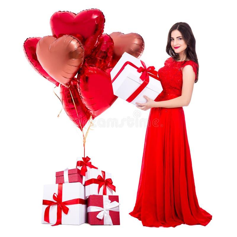 Valentinstagkonzept - Ganzaufnahme der netten Frau im roten Kleid mit den Geschenkboxen und Luftballonen lokalisiert auf Weiß stockbild