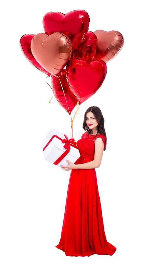 Valentinstagkonzept - Ganzaufnahme der Schönheit im roten Kleid mit den Geschenkboxen und Luftballonen lokalisiert auf Weiß lizenzfreie stockbilder