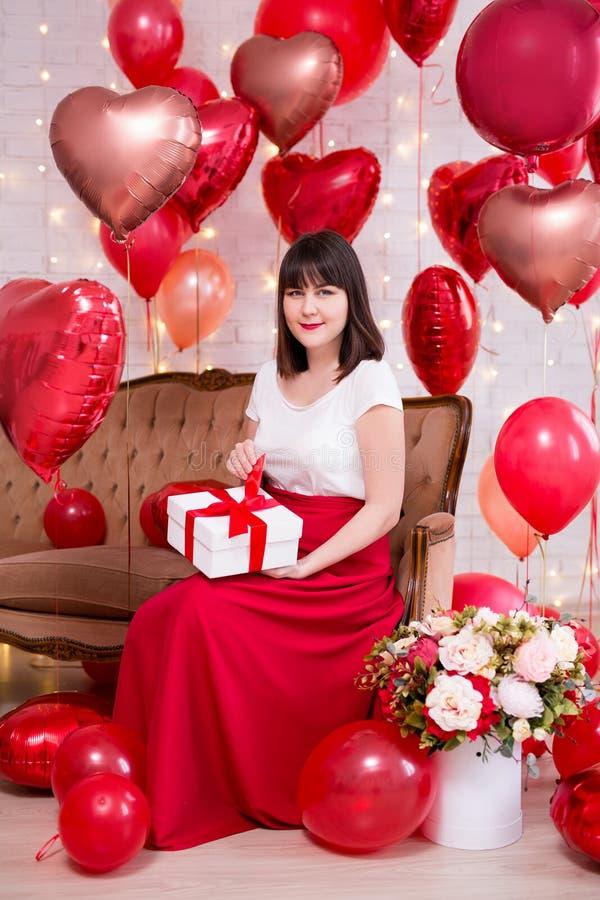 Valentinstagkonzept - junge Frau, die auf Weinlesesofa und öffnender Geschenkbox mit roten Herz-förmigen Ballonen sitzt stockfotos