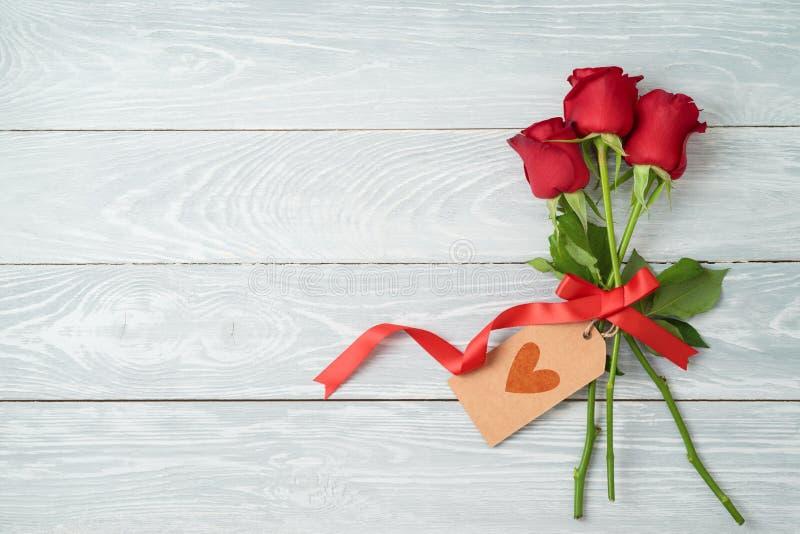 Valentinstagkonzept mit rosafarbenen Blumen und Geschenkumbau auf hölzernem Hintergrund lizenzfreie stockfotografie