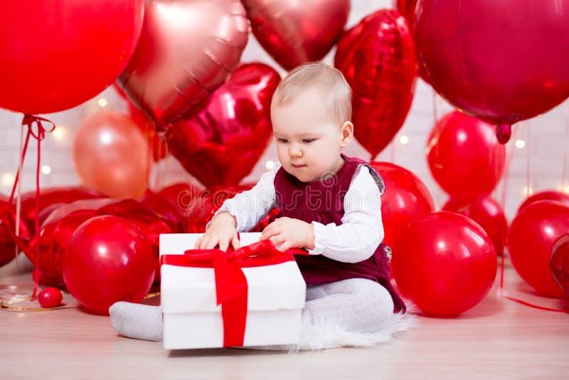 Valentinstagkonzept - nettes kleines Baby mit Geschenkbox und roten Ballonen lizenzfreies stockbild