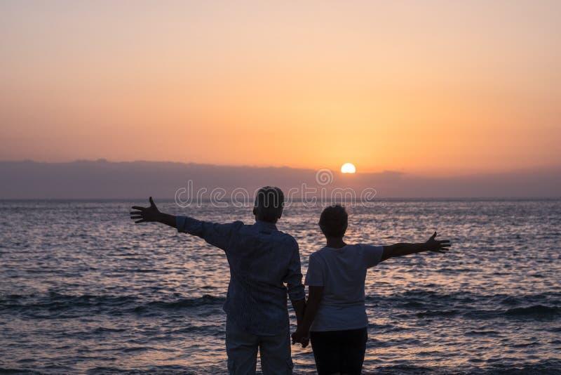 Valentinstagliebes-Paarkonzept mit den ?lteren gealterten offenen Armen der Leute mit Ozean und Sonnenuntergang vor ihnen - zusam lizenzfreies stockbild