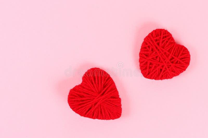 Valentinstagplan Rote selbst gemachte diy Herzen gemacht von der Pappe und vom Garn auf einem rosa Hintergrund St.-Valentinsgruß- stockfotografie