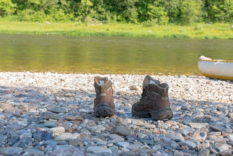 Valet av skor för turism och trekking Bruna kängor står på en stenig bank fotografering för bildbyråer