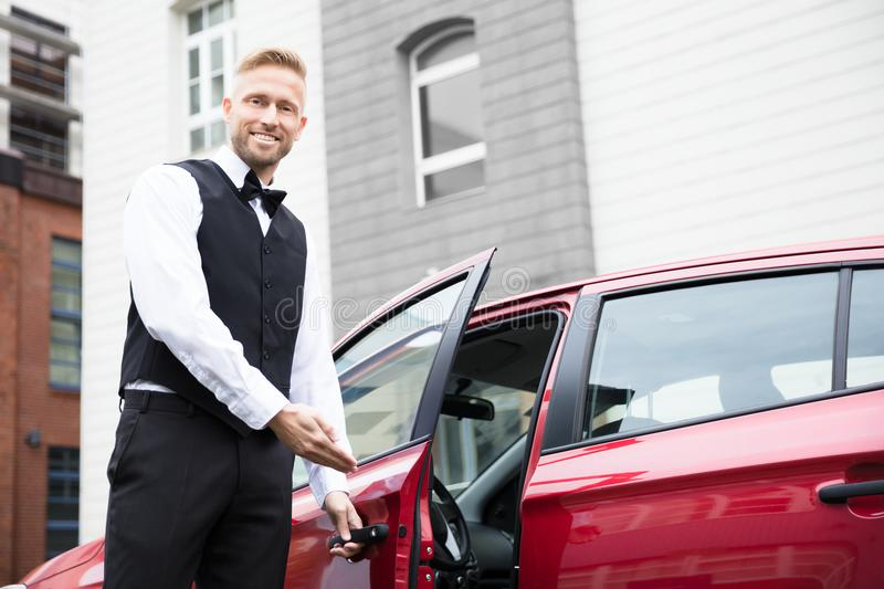 Valet masculin Opening Car Door photo stock
