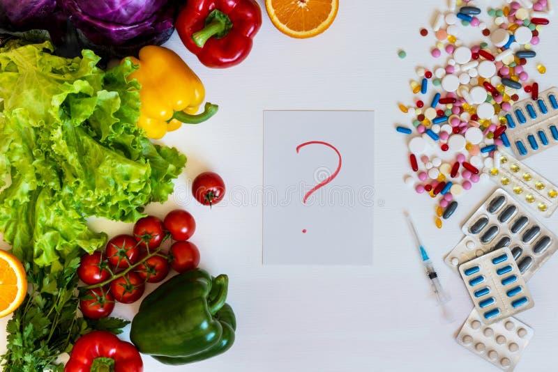 Valet mellan en sund livsstil och läkarbehandlinggrönsaker eller preventivpillerar arkivbild