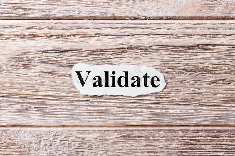 VALIDATE of the word on paper. concept. Words of VALIDATE on a wooden background stock photos
