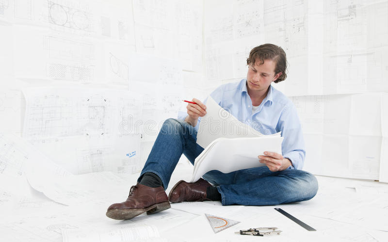 Validating technical drawings. Young mechanical engineer, surrounded by huge technical drawings, sitting on the floor on more designs, going over the technical stock images