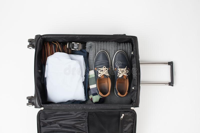 Valigia all'aperto del nero di viaggio con le cose su un bianco fotografia stock libera da diritti