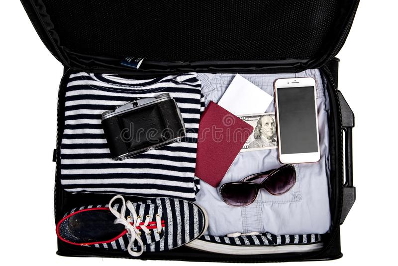 Valigia aperta con i vestiti, gli occhiali da sole, le scarpe, il passaporto, i soldi, il telefono cellulare e la macchina fotogr immagini stock