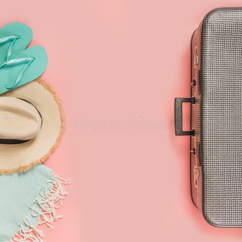 Valigia con l'attrezzatura femminile per la spiaggia sul rosa Vista superiore con lo spazio della copia Vacanze tropicali di esta fotografie stock