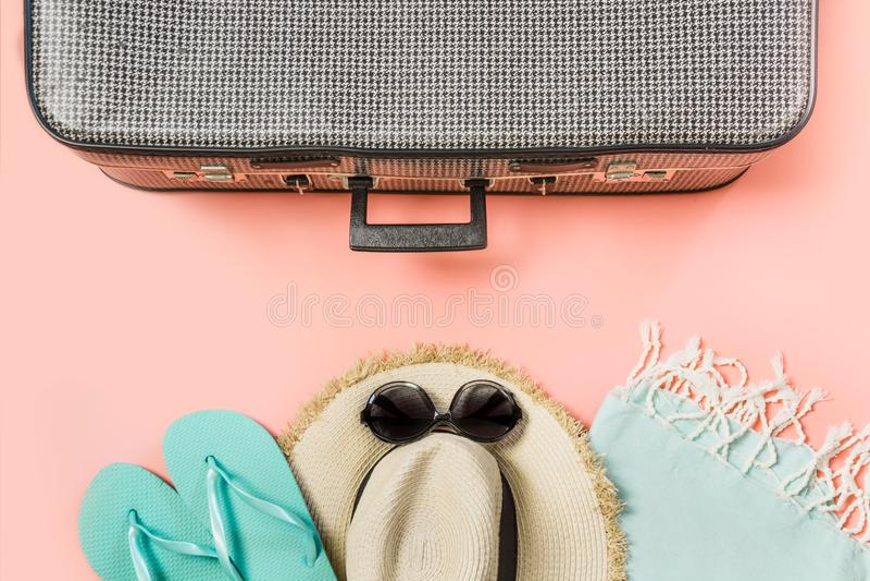 Valigia con l'attrezzatura femminile per la spiaggia sul rosa Vista superiore con lo spazio della copia Vacatons tropicali di est immagine stock libera da diritti