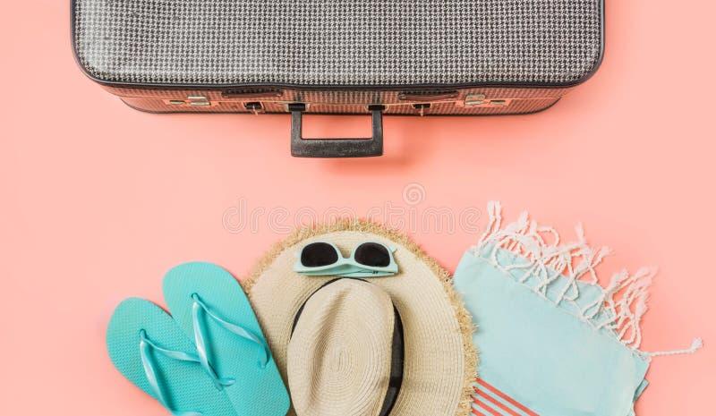 Valigia con l'attrezzatura femminile per la spiaggia sul rosa Vista superiore con lo spazio della copia Vacatons tropicali di est fotografia stock