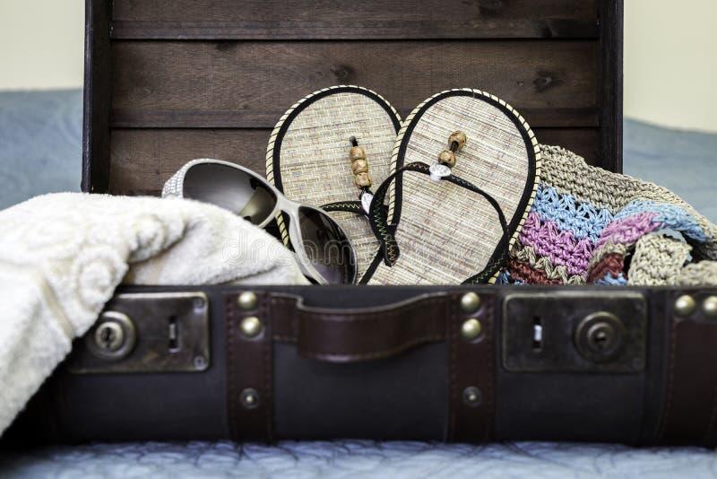 Valigia d'annata aperta ed imballata con gli elementi della spiaggia, concep di viaggio immagini stock libere da diritti