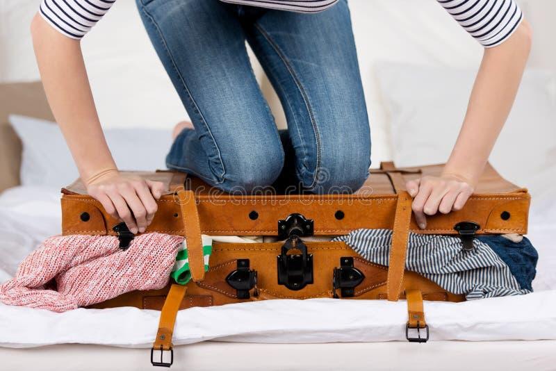 Valigia dell'imballaggio della giovane donna sul letto fotografia stock