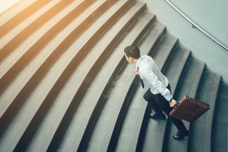 Valigia e funzionamento della tenuta dell'uomo d'affari sulle scale immagini stock libere da diritti