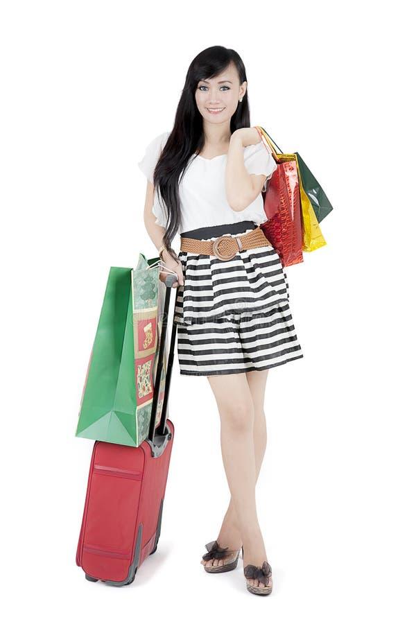 Valigia e sacchetti della spesa graziosi della tenuta della ragazza fotografie stock