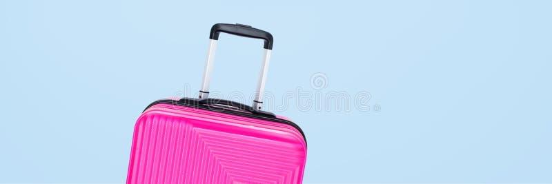 Valigia rosa dell'insegna isolata su fondo blu fotografia stock
