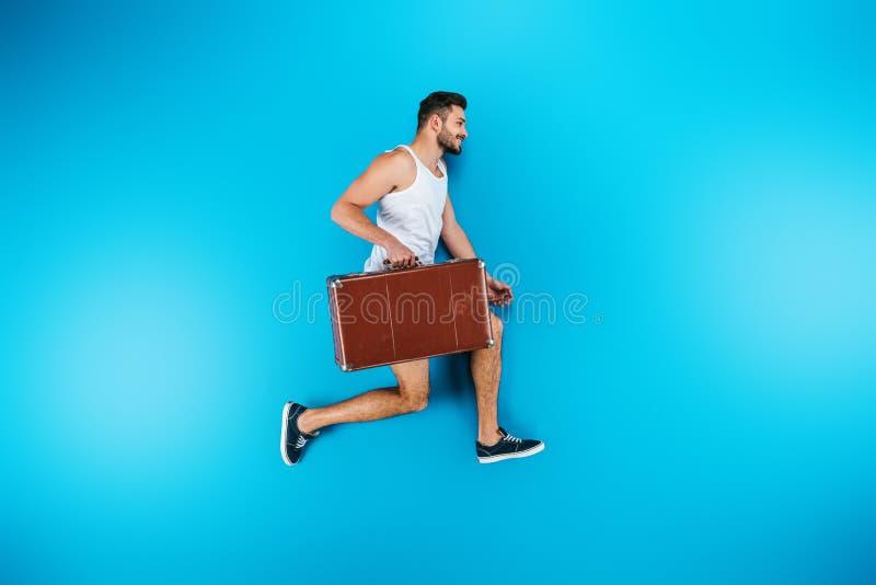 valigia sorridente bella e correre della tenuta del giovane fotografia stock