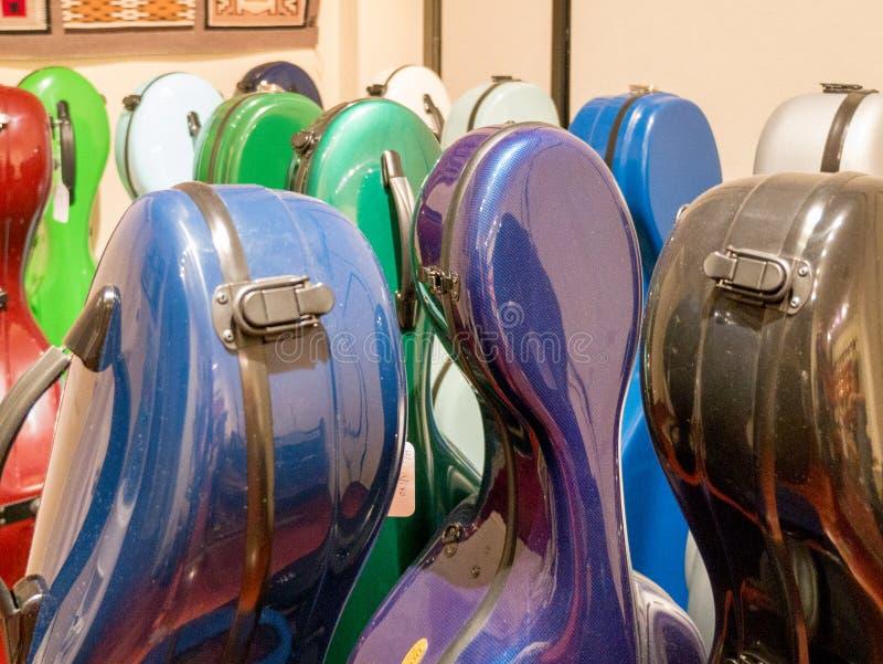 Valigie multicolori variopinte del violoncello che stanno sull'esposizione immagine stock