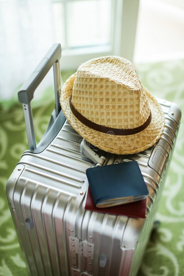 Valise argentée de touristes avec le chapeau, le portefeuille et le passeport en osier là-dessus Préparez pour se déplacer Vue su image stock