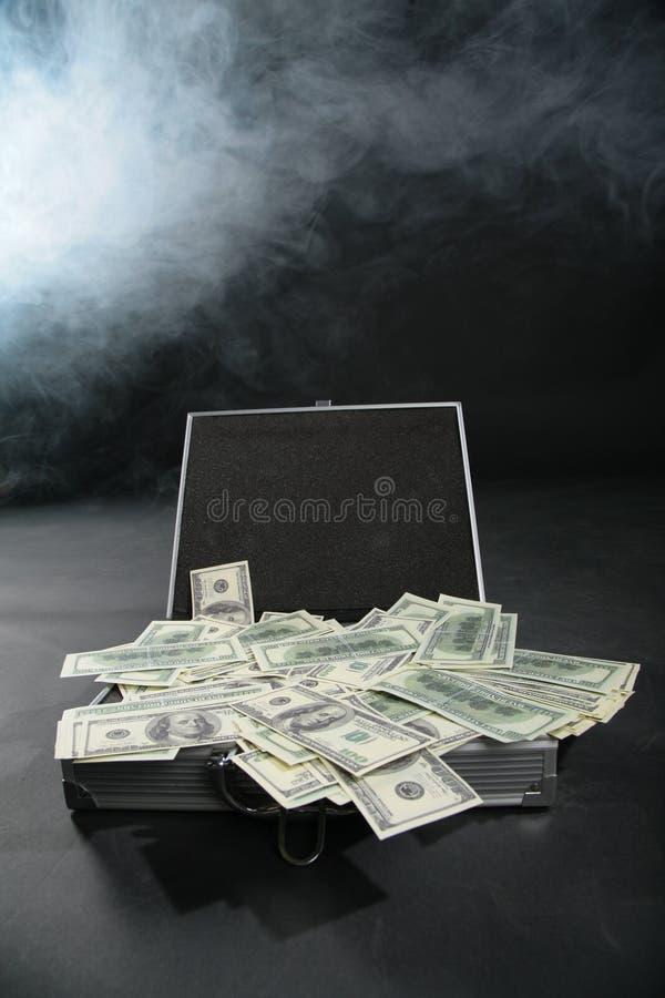 Valise avec des dollars contre la fumée photos stock