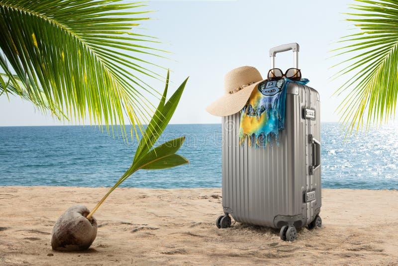 valise avec le chapeau, le pareo et les lunettes de soleil sur la plage tropicale ensoleillée image libre de droits